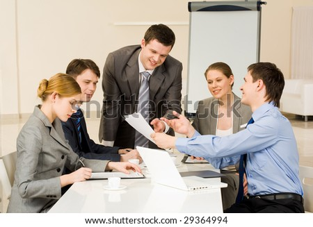 Portrait of confident man showing document to co-workers and interacting with them