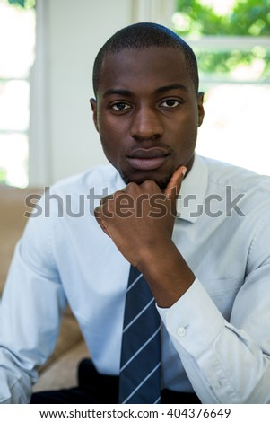 Portrait of confident man sitting with hand on chin at home