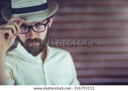 Portrait of confident man wearing eyeglasses and hat against wall