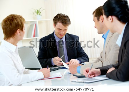 Portrait of confident manager looking at document and giving consulting to business people