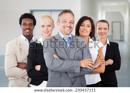 Portrait of confident manager standing arms crossed with team in office