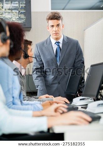 Portrait of confident manager standing in front of customer service representatives in office - stock photo