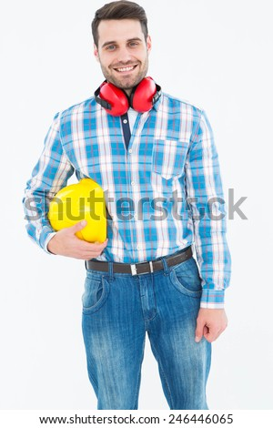 Portrait of confident manual worker with hardhat and ear muffs on white background - stock photo