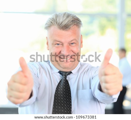 Portrait of confident mature businessman giving you thumbs up - stock photo