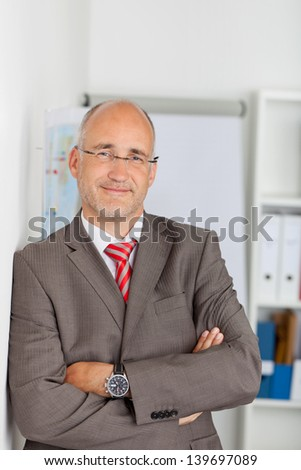 Portrait of confident mature businessman leaning on wall at office - stock photo