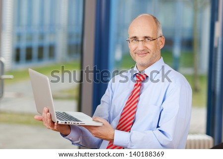 Portrait of confident mature businessman with laptop in office - stock photo