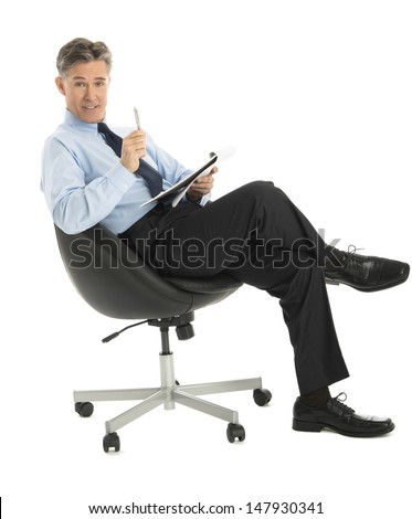 Portrait of confident mature businessman with note pad and pen sitting on office chair against white background