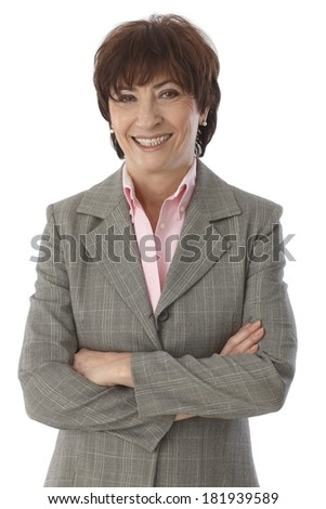 Portrait of confident, mature businesswoman standing arms crossed, smiling happy. - stock photo
