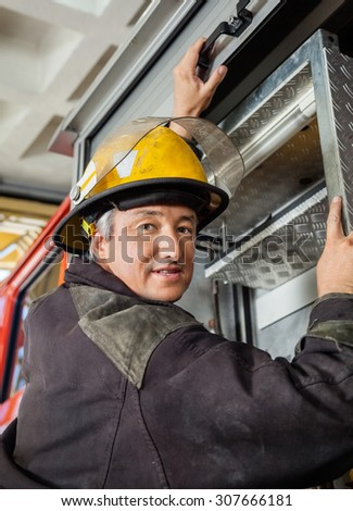 Portrait of confident mature fireman climbing truck at fire station