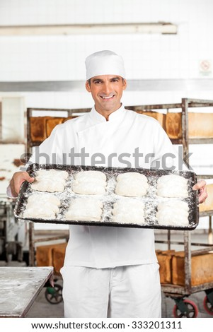 Portrait of confident mature male baker showing dough in baking tray at bakery