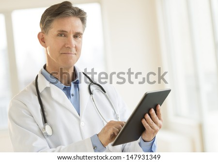 Portrait of confident mature male doctor holding digital tablet while standing in clinic