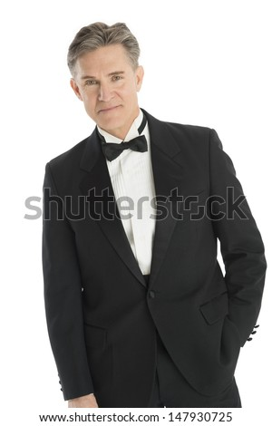 Portrait of confident mature man in tuxedo standing against white background - stock photo