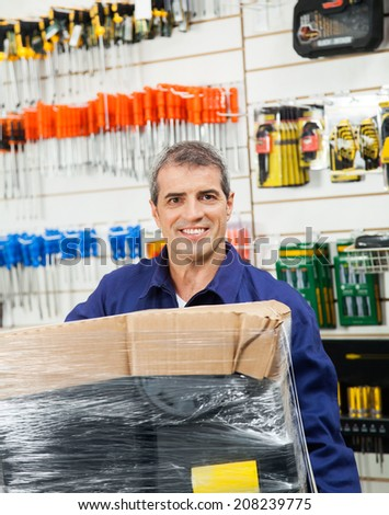 Portrait of confident mature worker with wrapped tool package in hardware shop
