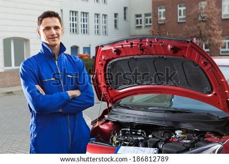 Portrait of confident mechanic with arms crossed standing by car on street - stock photo