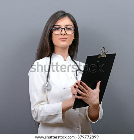 Portrait of confident medical doctor woman writing on clipboard against gray background - stock photo