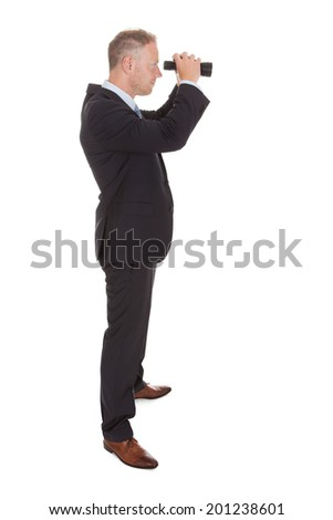 Portrait of confident mid adult businessman looking through binoculars over white background