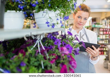 Portrait of confident mid adult florist holding digital tablet while standing by flower trolley in shop - stock photo
