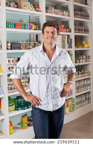 Portrait of confident mid adult man with hands on hips in supermarket
