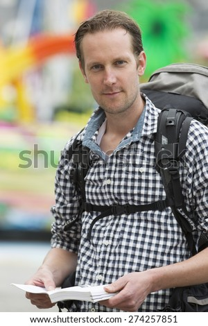 Portrait of confident mid adult tourist holding book while carrying backpack - stock photo