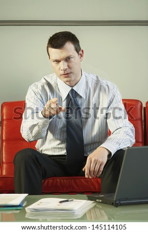 Portrait of confident middle aged businessman pointing while sitting on red couch in office