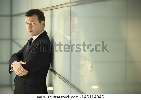 Portrait of confident middle aged businessman with arms crossed leaning on glass wall in office - stock photo