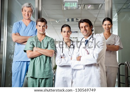 Portrait of confident multiethnic medical professionals standing together with arms crossed - stock photo