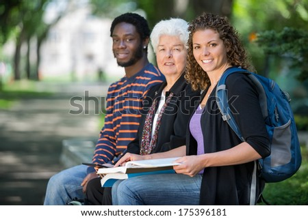Portrait of confident multiethnic university students sitting on campus