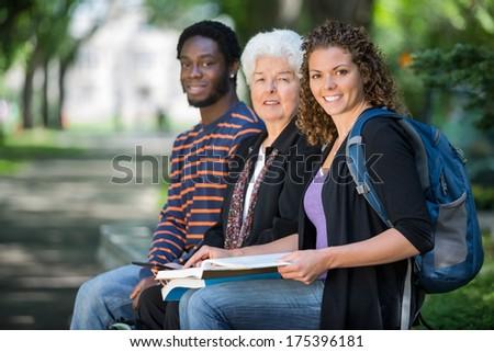 Portrait of confident multiethnic university students sitting on campus - stock photo