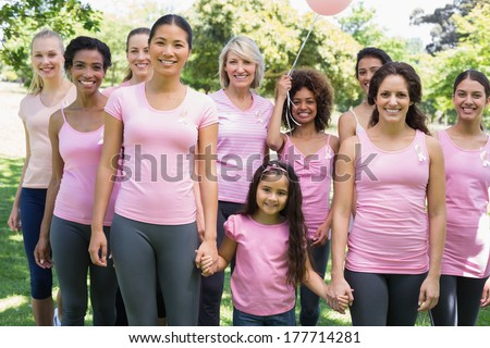 Portrait of confident multiethnic women and girl supporting breast cancer awareness at park - stock photo