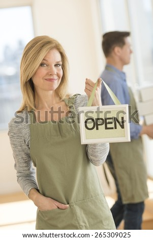 Portrait of confident owner wearing apron while holding open sign in cafe - stock photo
