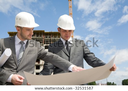 Portrait of confident partners looking at new construction plan and discussing it - stock photo