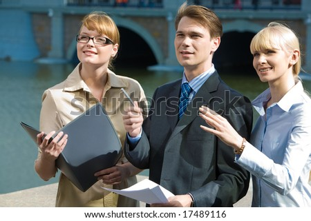 Portrait of confident partners pointing at something outdoors and looking at it - stock photo