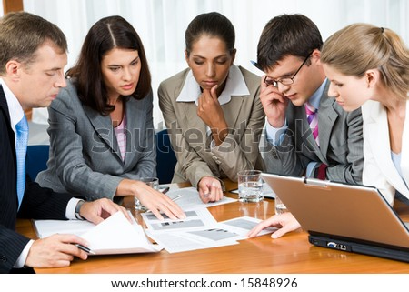 Portrait of confident people looking seriously at business papers during working meeting - stock photo