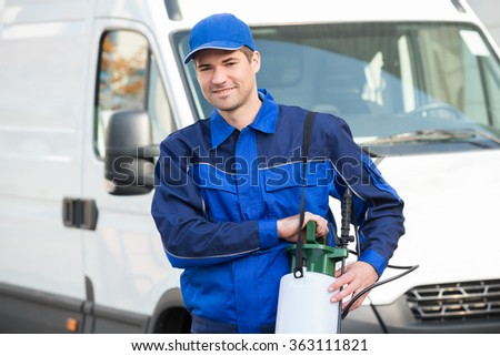 Portrait of confident pest control worker with pesticide against truck