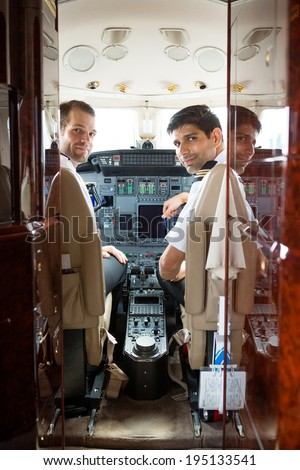 Portrait of confident pilot and copilot in corporate plane cockpit - stock photo