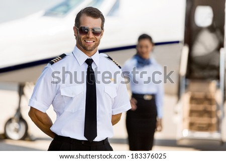 Portrait of confident pilot standing with stewardess and private jet in background at terminal - stock photo