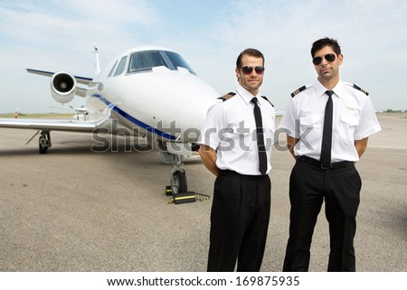 Portrait of confident pilots standing in front of private jet - stock photo