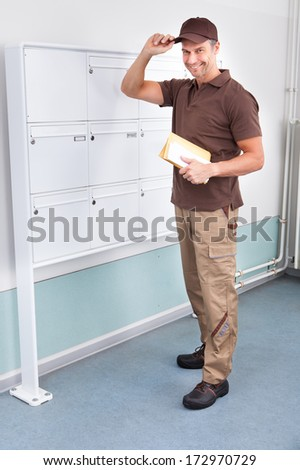Portrait Of Confident Postman Holding His Cap - stock photo