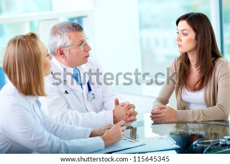 Portrait of confident practitioners consulting patient in hospital