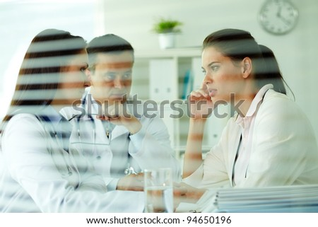 Portrait of confident practitioners consulting patient in medical office - stock photo