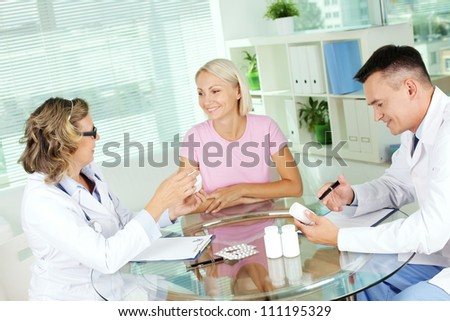 Portrait of confident practitioners describing new vitamins to patient in hospital - stock photo