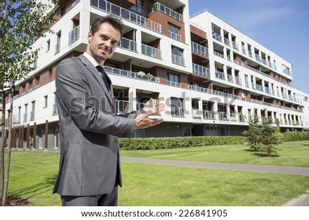 Portrait of confident real estate agent showing office building - stock photo