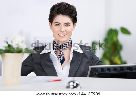 Portrait of confident receptionist smiling at counter - stock photo