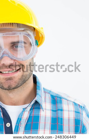 Portrait of confident repairman wearing protective glasses and hard hat on white background - stock photo
