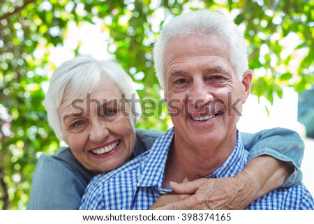 Portrait of confident retired couple embracing - stock photo