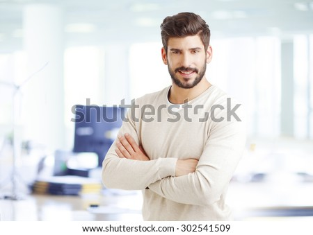 Portrait of confident sales man standing at office with arms crossed and smiling while looking at camera. - stock photo