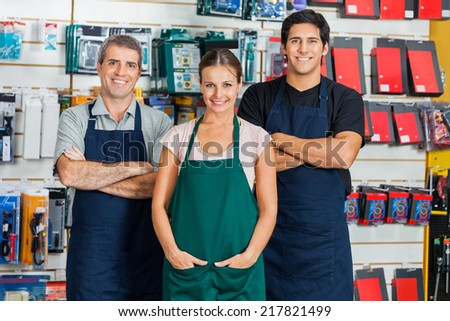 Portrait of confident salespeople standing in hardware store - stock photo