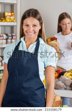 Portrait of confident saleswoman with female customer in background at supermarket - stock photo