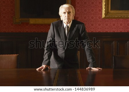 Portrait of confident senior businessman leaning hands at conference table - stock photo