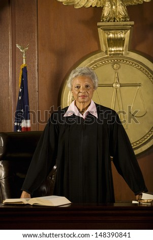 Portrait of confident senior female judge standing in court room - stock photo